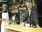 LOCAL HEROES Jon Michael Hill, left, helps out Uptown vendor McKean in Superior Donuts.