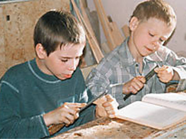 LITTLE MAN, WHITTLE NOW? Spiridonov, right, conducts his own woodworking class.