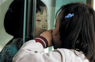 NO PANE, NO GAIN Kim Song-hee, left, peers through the window at her big sister.