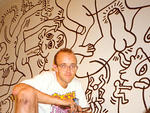 21. See the work of an iconic New York artist. Pictured: Keith Haring in front of his mural Once Upon a Time at the LGBT Center