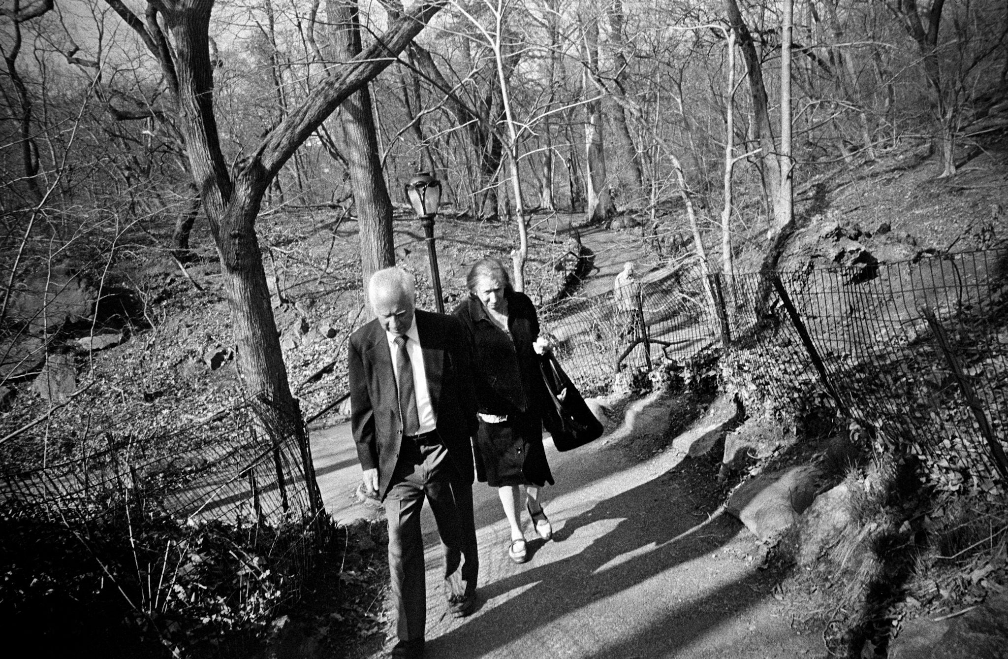 A couple walks along a path through the Ramble.