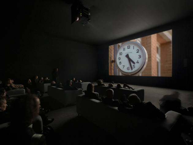An audience takes in a scene from Christian Marclay's The Clock