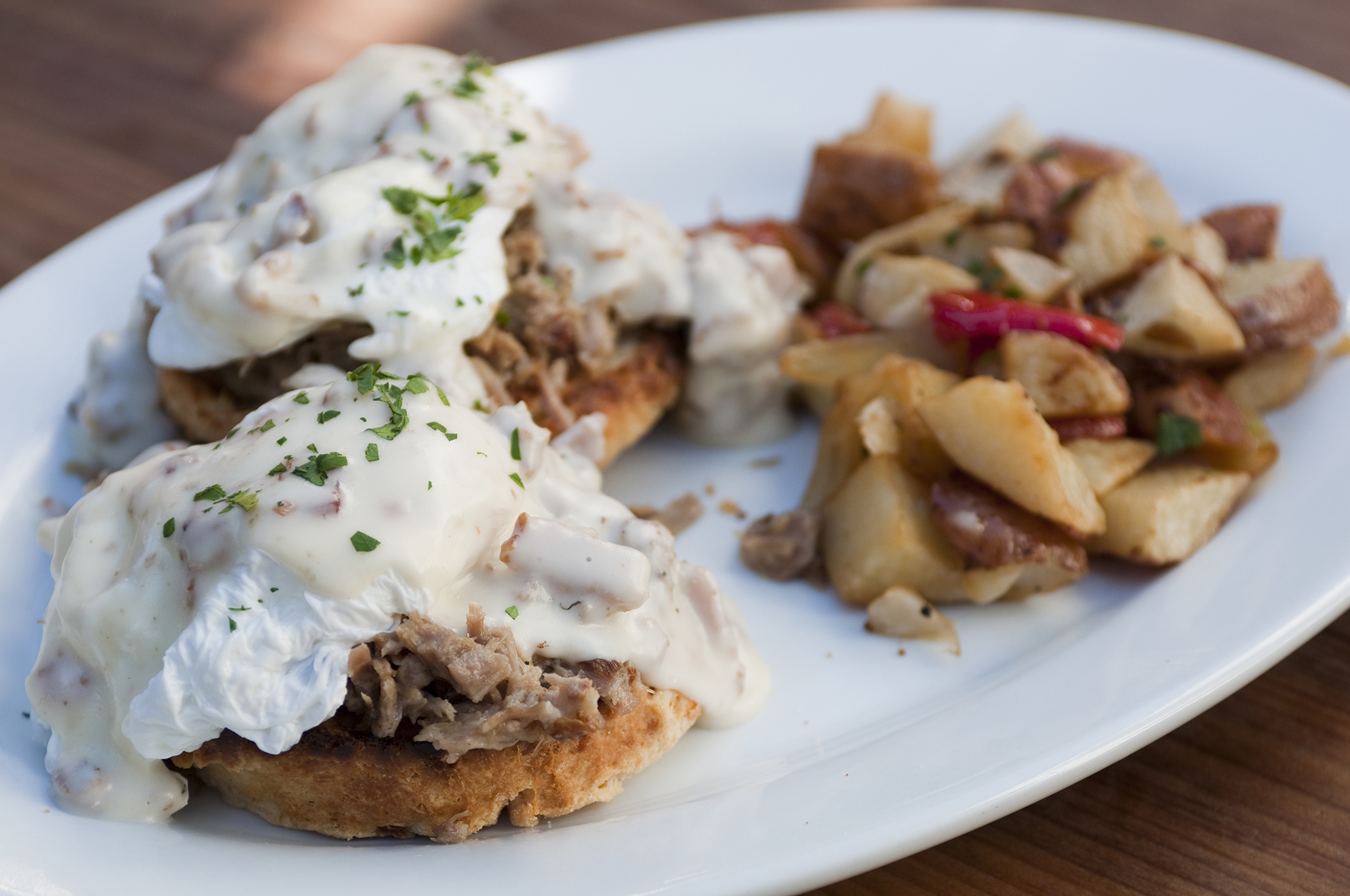 Pulled pork with an Asiago biscuit, poached eggs, country gravy and potatoes at Maximilliano
