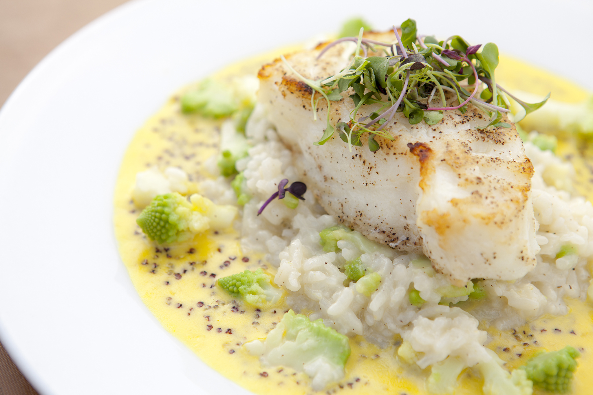 Chilean sea bass with risotto and saffron quinoa at Tra di noi