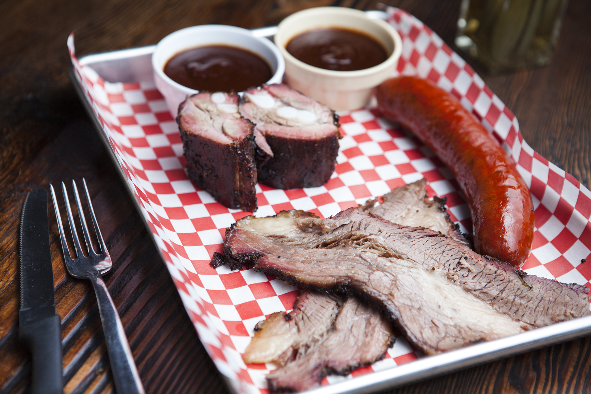 <p><em>Clockwise from top</em>: Brisket, rib tips and hot link at Bludso's Bar-&amp;-Que</p>