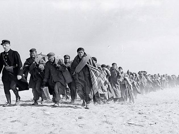 ( Robert Capa, 'Exilés républicains marchant sur la plage vers un camp d'internement', Le Barcarès, France, mars 1939 / © International Center of Photography / Magnum)