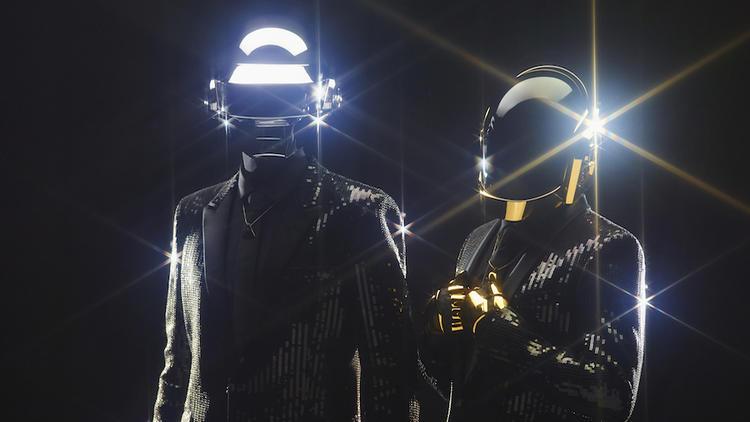Daft Punk dressing in shining metal helmets against a black background