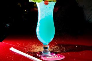 Blue Hawaii (Ingredients: suc de llimona, pinya, xarop de sucre, curaçao blau, rom, vodka, gel picat en abundància, rodanxa de llimona i l'inevitable i imprescindible para-sol.)