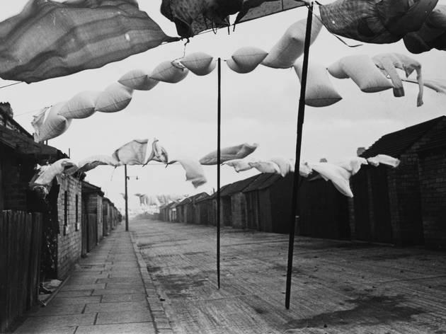 Humphrey Spender (Ashington – Washing in road between terraced housing, 1937/38)