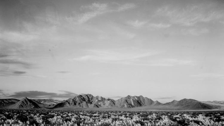 Near death Valley National Monument (More distant view of mountains, desert, shrubs highlighted in foreground)