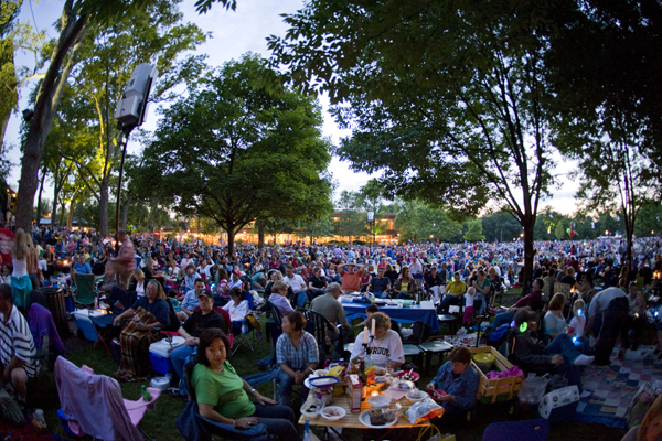 Sit on the lawn at an outdoor concert