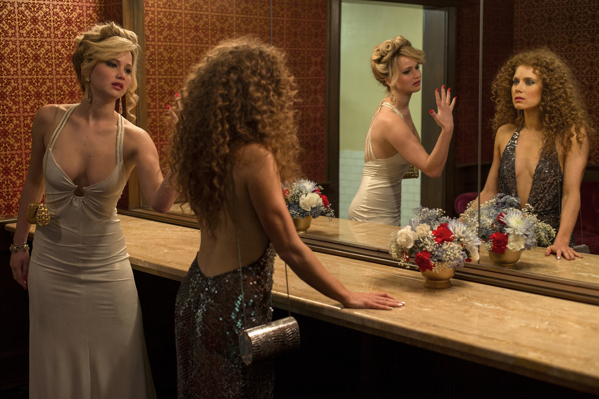 Rosalyn Rosenfeld (Jennifer Lawrence) & Sydney Prosser (Amy Adams) in the Grand Old AC Hotel powder room in Columbia Pictures' AMERICAN HUSTLE.  (Jennifer Lawrence dress: made for film, jewelry, shoes: vintage / Amy Adams dress: made for film, jewelry, sh