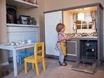 Gracie Samuel plays in the play kitchen her mother, Dawn Samuel made for her out of a tv stand. Lindsay Pierce, The Denver Post