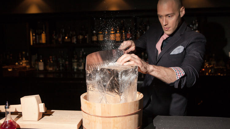 Michael Simon cutting down ice cubes at Charcoal bar.