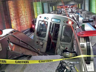 "A Chicago Transit Authority train car rests on an escalator at the O'Hare Airport station after it derailed early Monday, March 24, 2014, in Chicago. More than 30 people were injured after the train ""climbed over the last stop, jumped up on the sidewalk a"