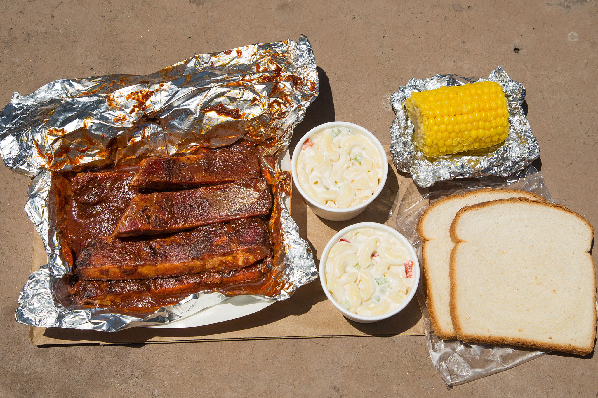 Pork ribs, macaroni salad, white bread, and corn on the cob at Phillip'sBBQ