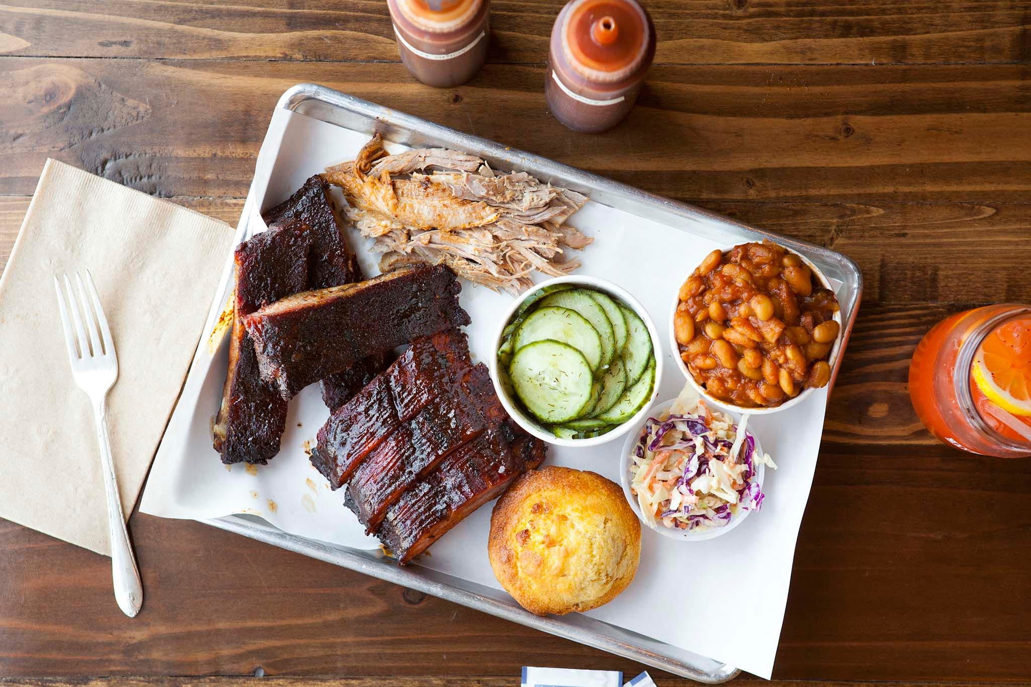 Spence's Platter of Pork with cucumber salad, cornbread, cole slaw, and baked beans
