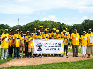 Onlookers welcome the Jackie Robinson West Little League team back to the city with a parade on August 27, 2014.