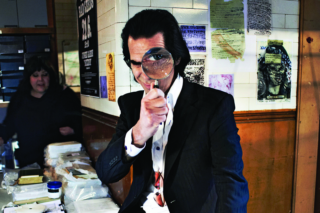 Nick Cave plays with a magnifying glass at his archives in Draft
