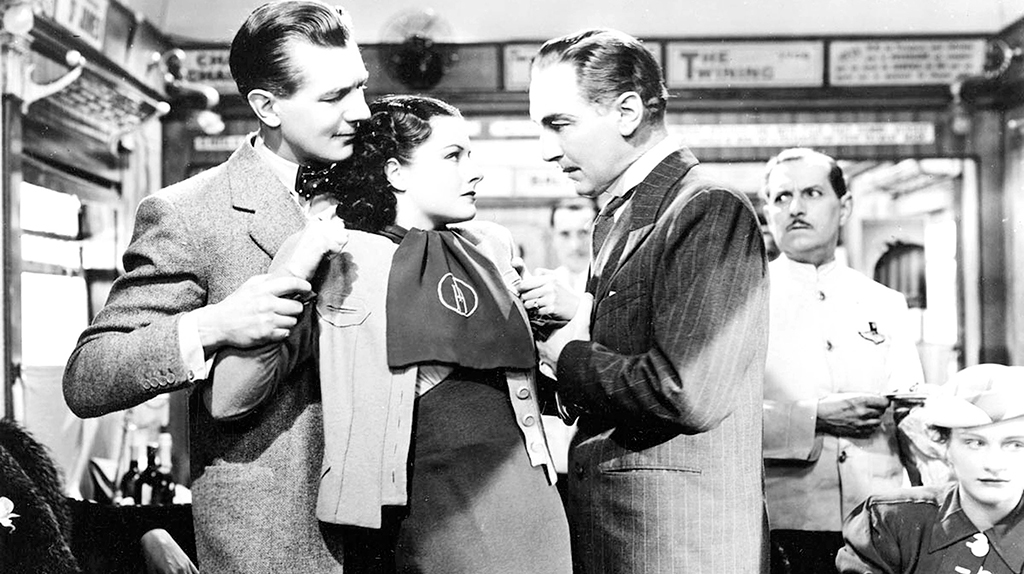 A still from the black and white film The Lady Vanishes of two men interrogating a women on a train
