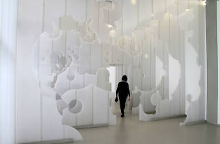 Layered wall installation with woman walking through