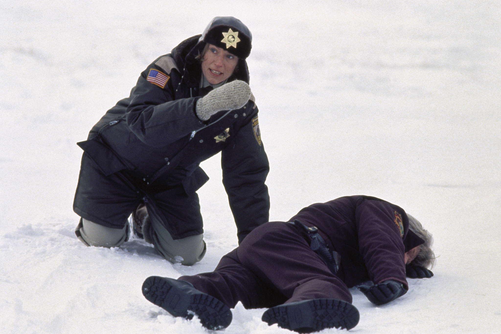 Frances McDormand in Fargo cop unifmorm, crouching in snow over a slumped body