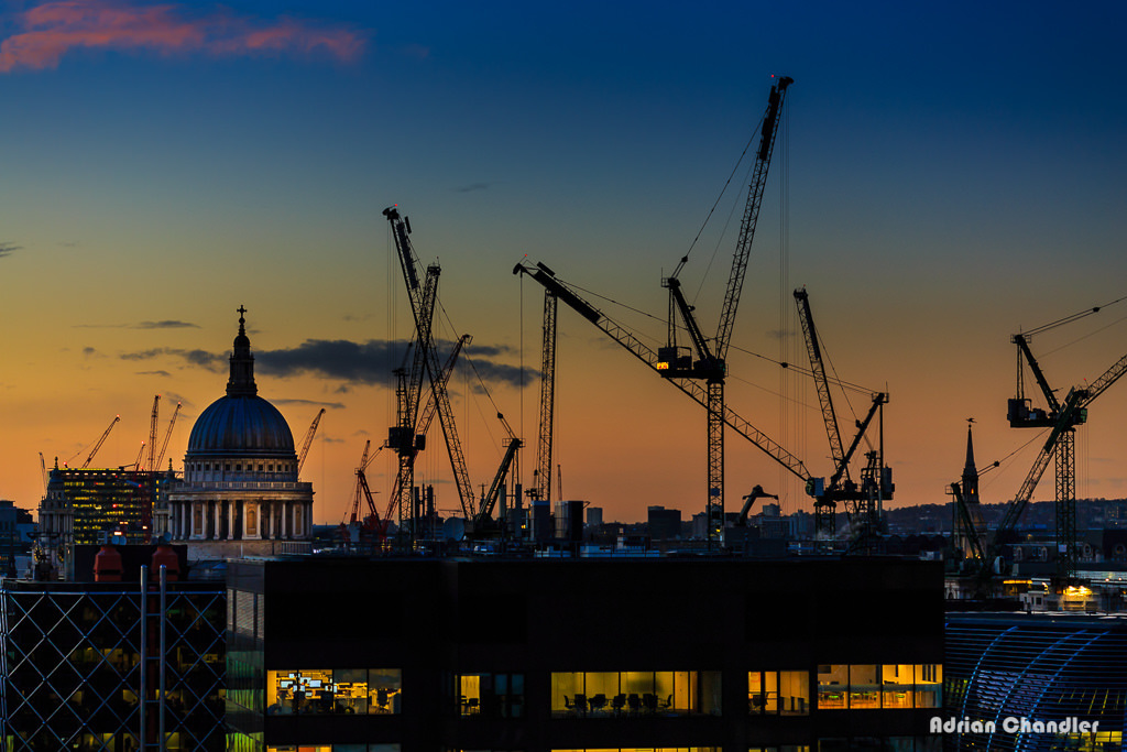 Sun sets over St. Paul's and several construction cranes.