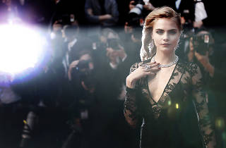 Cara Delevingne stands in front of a wall of photographers at Cannes Film Festival