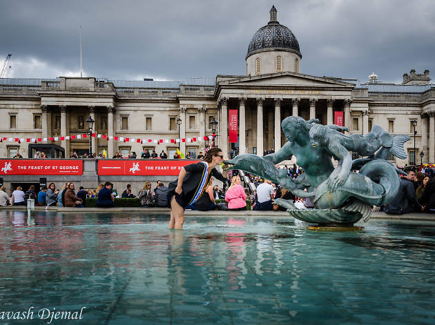 A woman paddles in the Trafalgar Square fountain and kisses a dolphin statue.