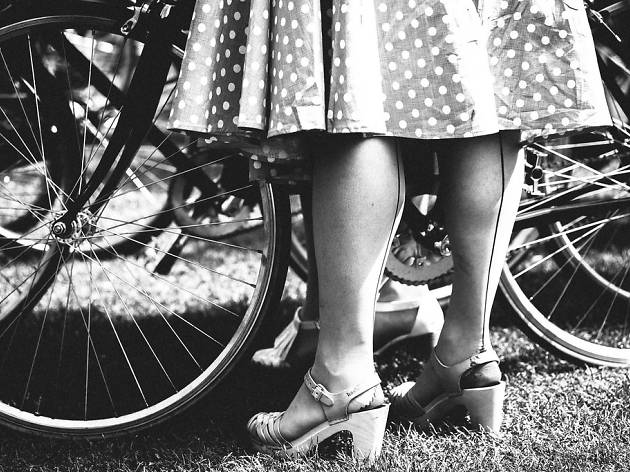 A woman in a polka-dot dress stands by her bicycle during the Tweed Run 2015.