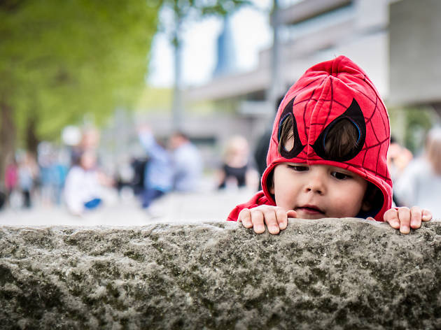 101 things to do in London with kids, A child dressed as Spiderman peers over a wall on the South Bank, London.