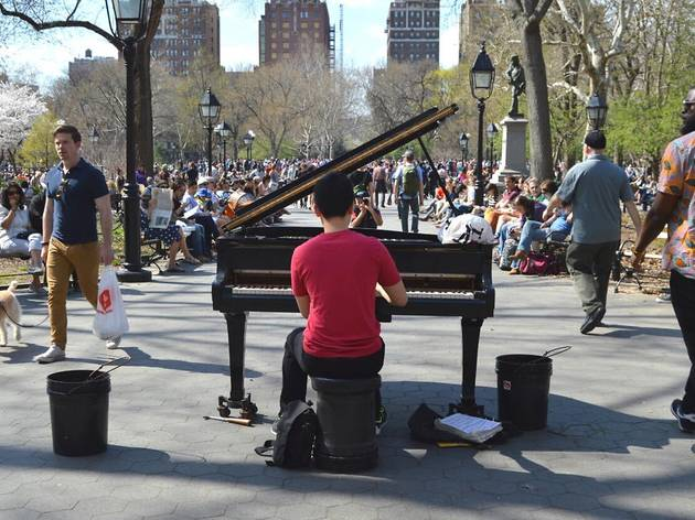 A man plays a piano in Washington Square Park.