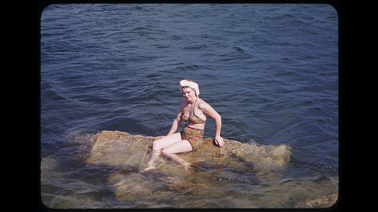 A swimmer poses astride rock off Promontory Point.