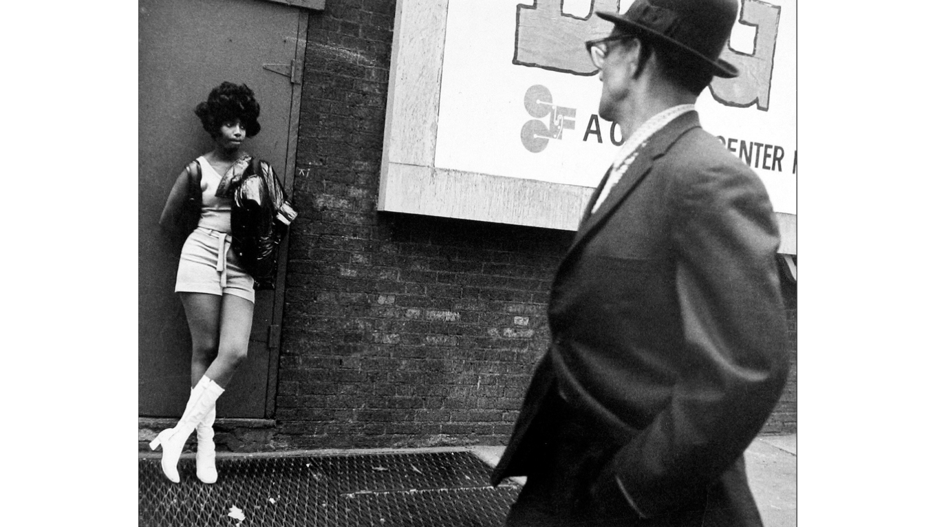 Leon Levinstein, Man Wearing Glasses and Hat looking at Woman Leaning Against a Door, 1965–1975
