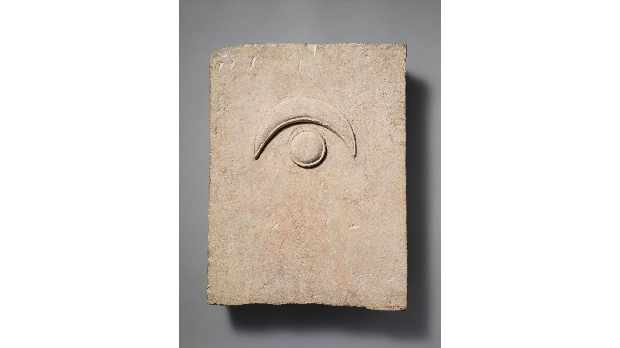 Fragment of a limestone funerary stele with a disk and a crescent