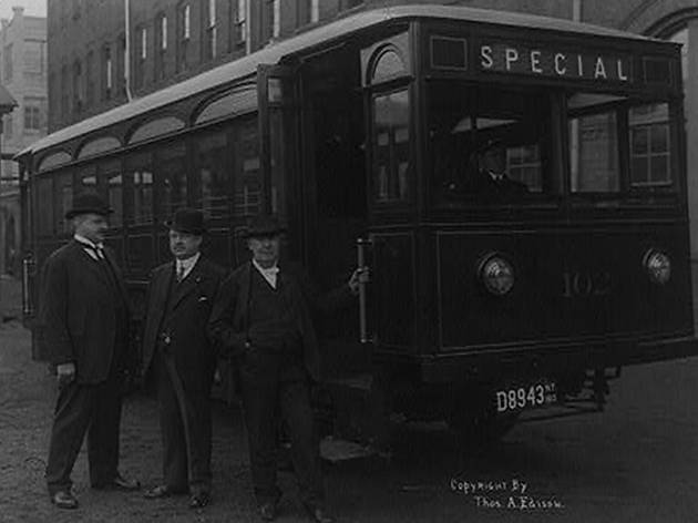 1913, Thomas Edison and two other men standing outside of bus