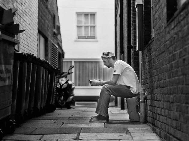 Man taking a smoke break alone in an alley.