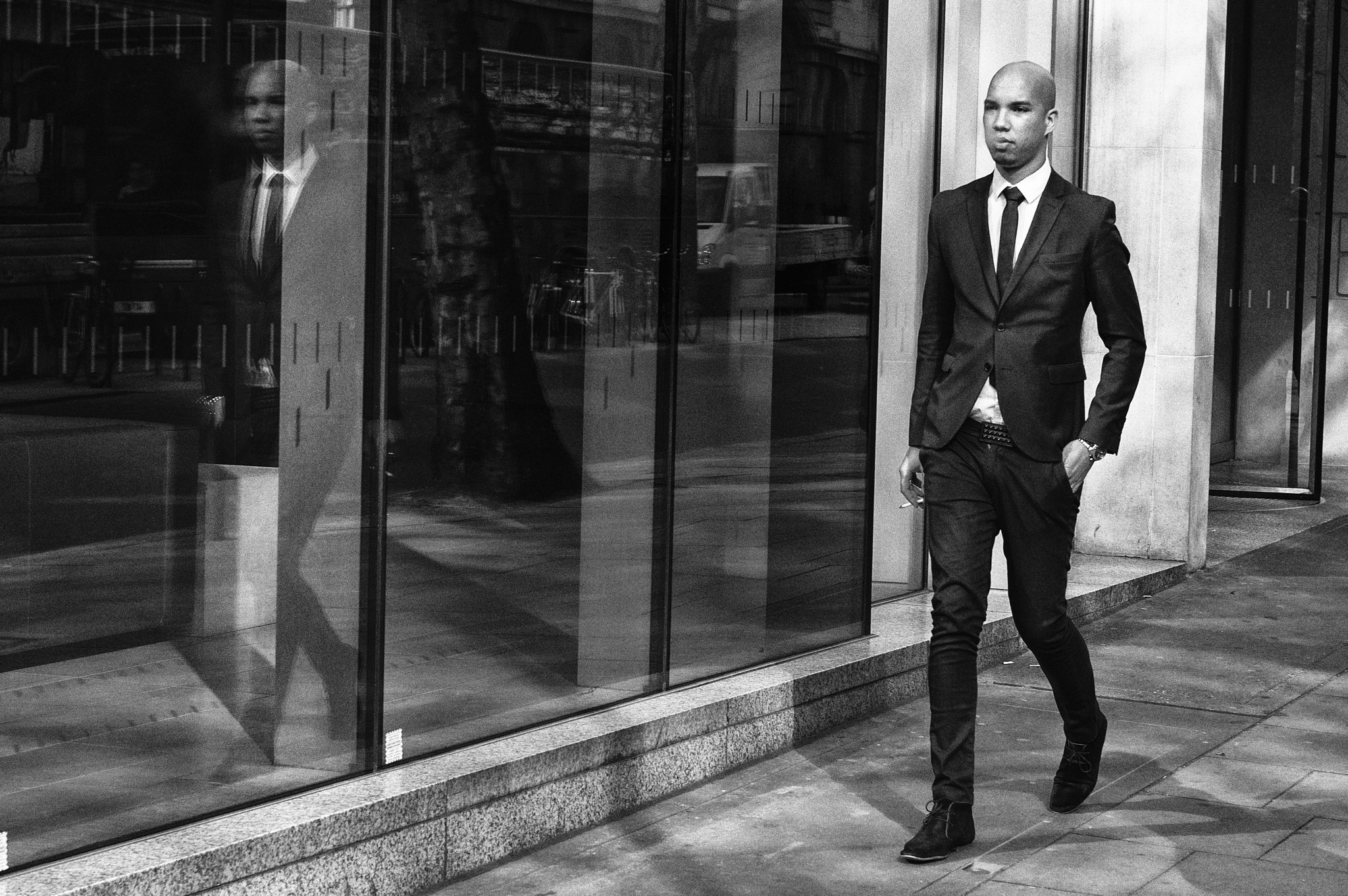 A man in a suit smoking and walking.