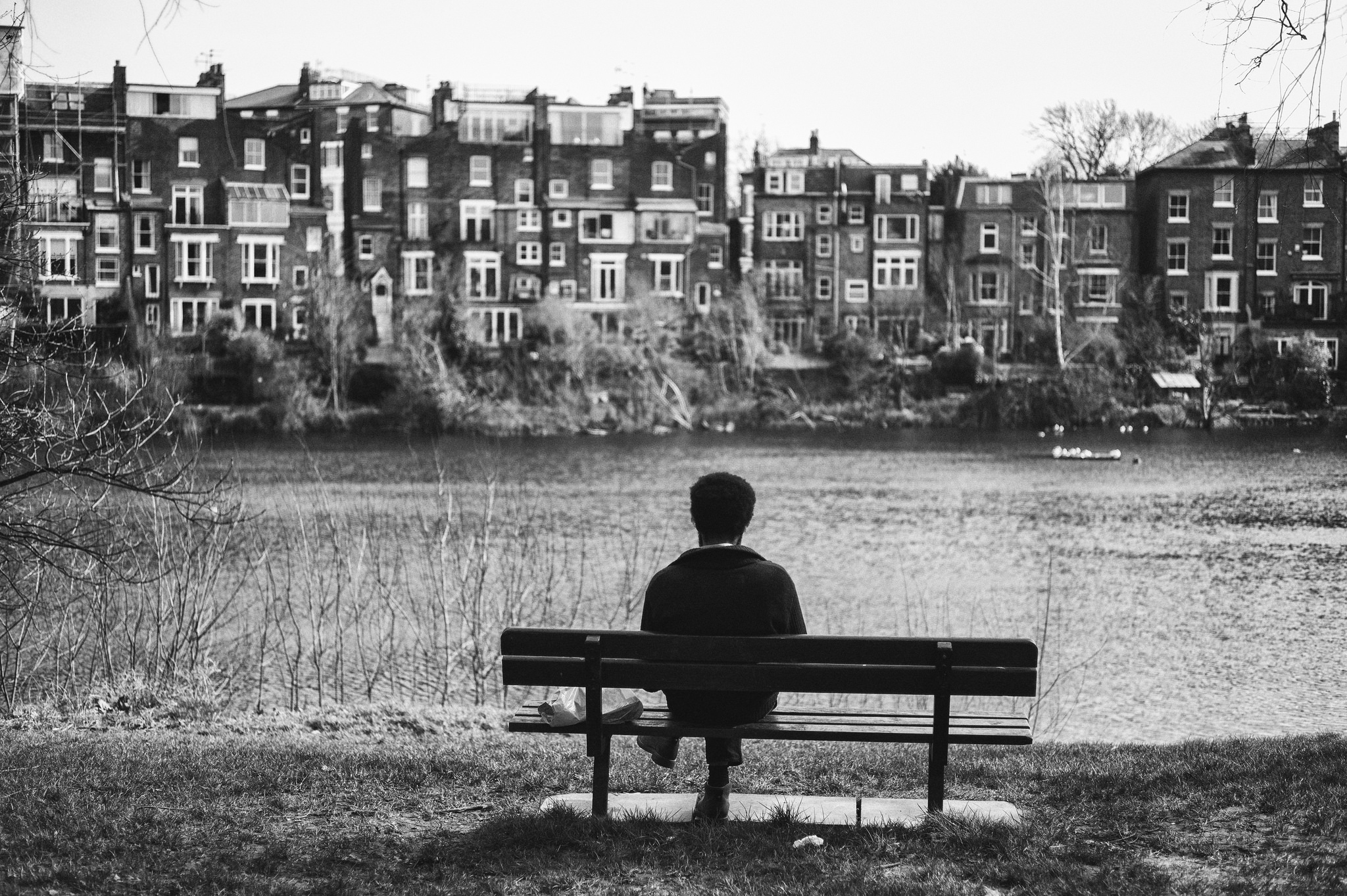 A man sits on a bench looking over Hampstead Ponds.