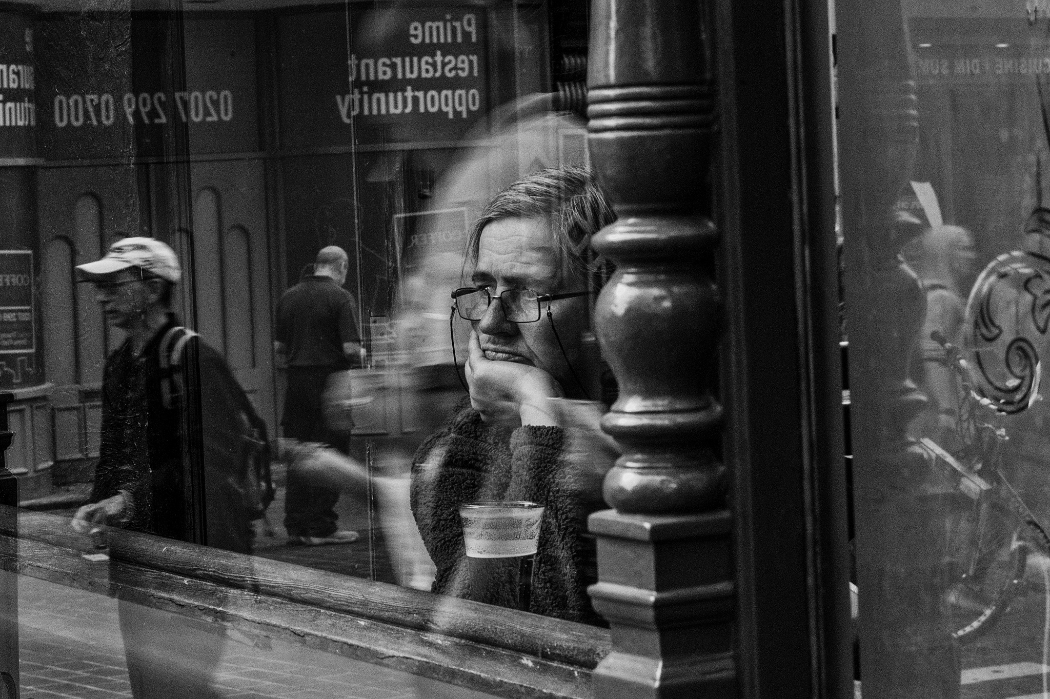 A man looks through a window in this black and white photograph.