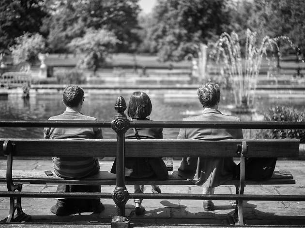 Three people sitting on a bench.