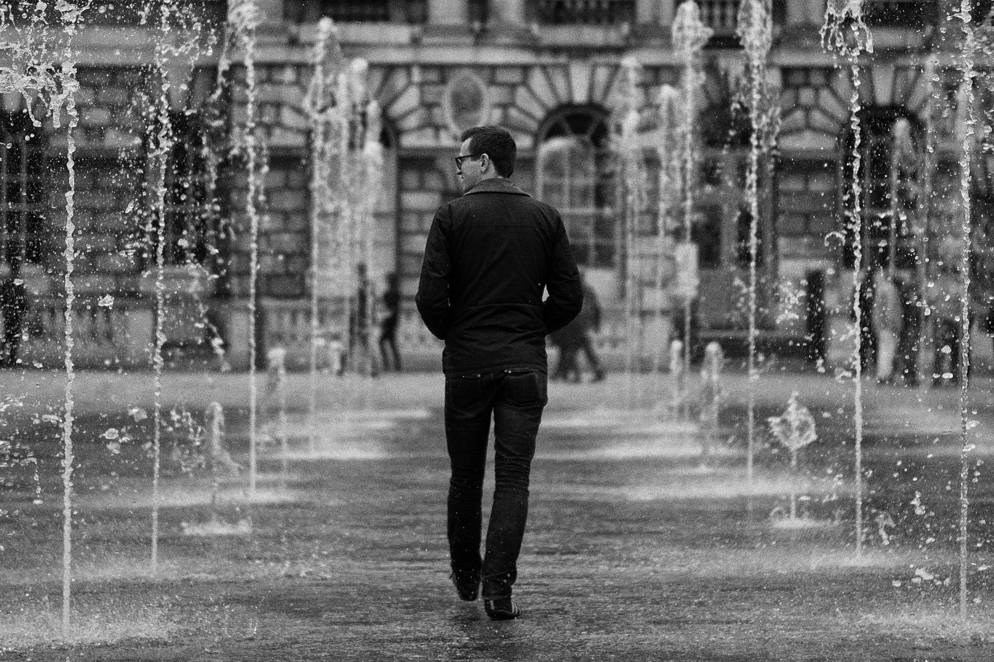 A man walks through fountains.