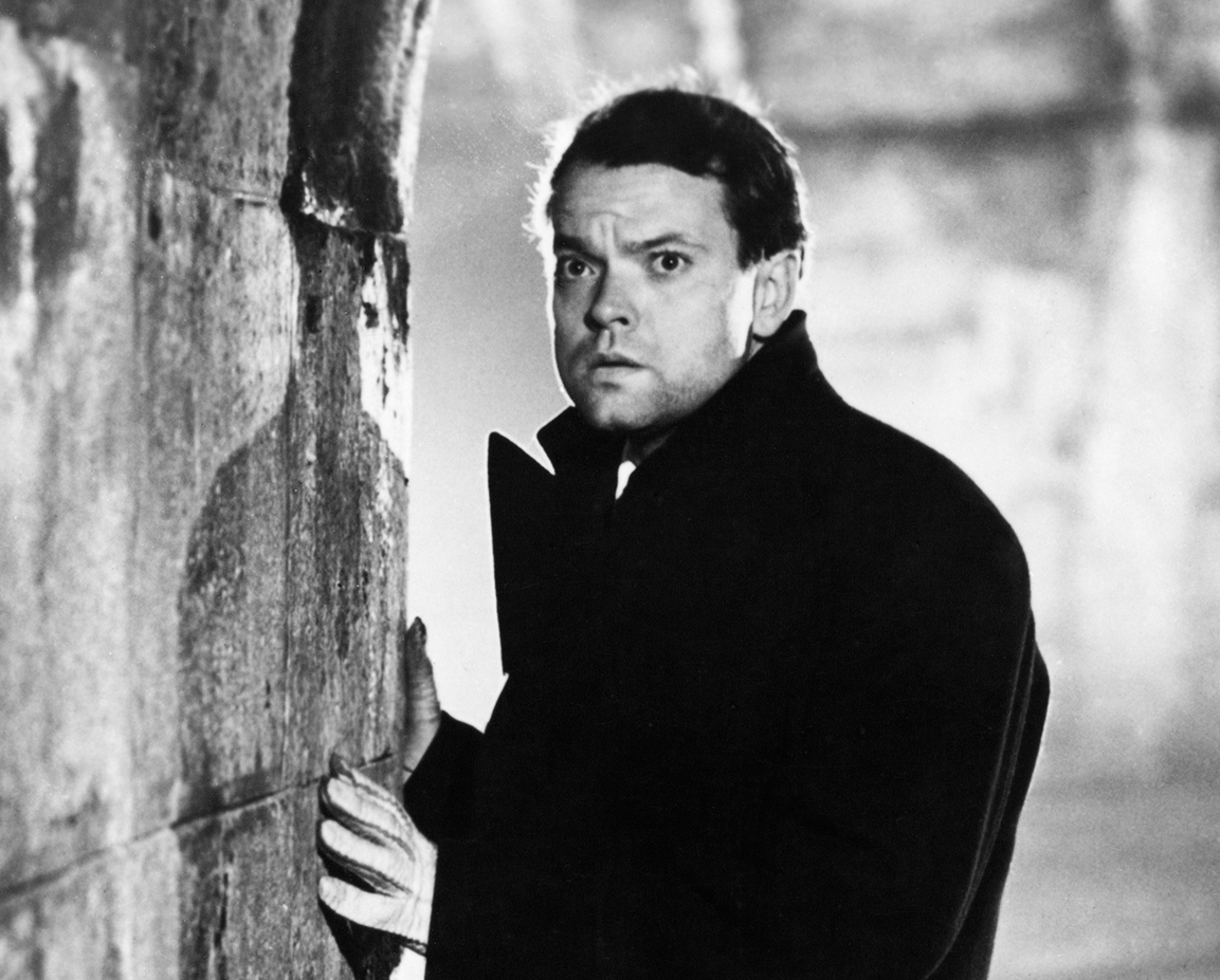 A still from the black and white film The Third Man or Orson Welles in a black coat against a wall