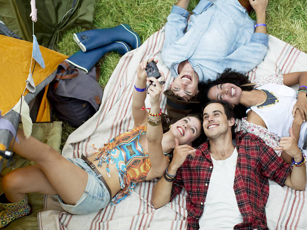 Friends taking self-portrait on blanket outside tent at music festival