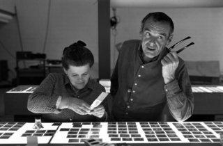 (Charles and Ray Eames selecting slides. © Eames Office LLC.)