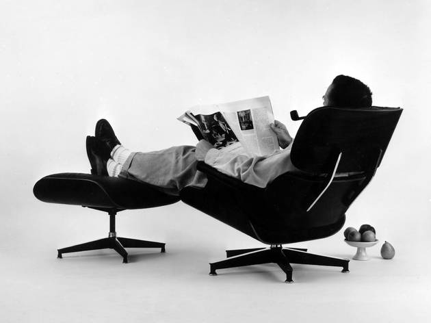 (Charles Eames in the plywood Lounge and Ottoman. Photograph for an advertisement,1956 © Eames Office LLC.)