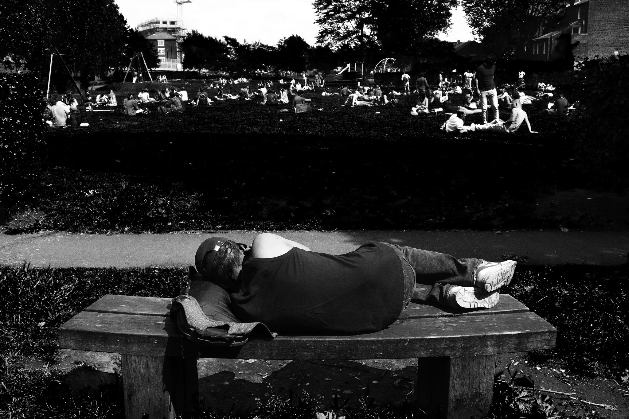 A man sleeps on a bench in a Shoreditch park.