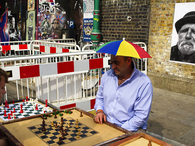A man plays chess while wearing an umbrella hat.