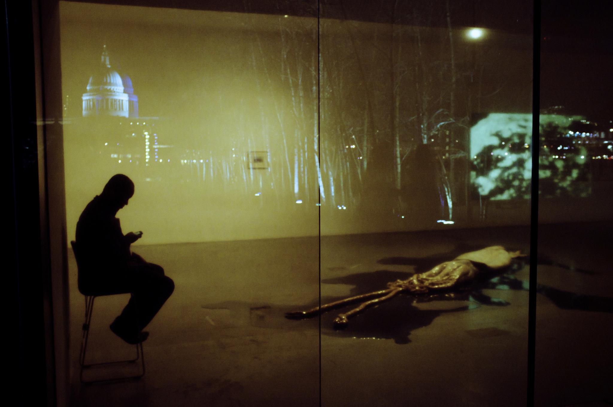 A man texts while sat near a giant squid.