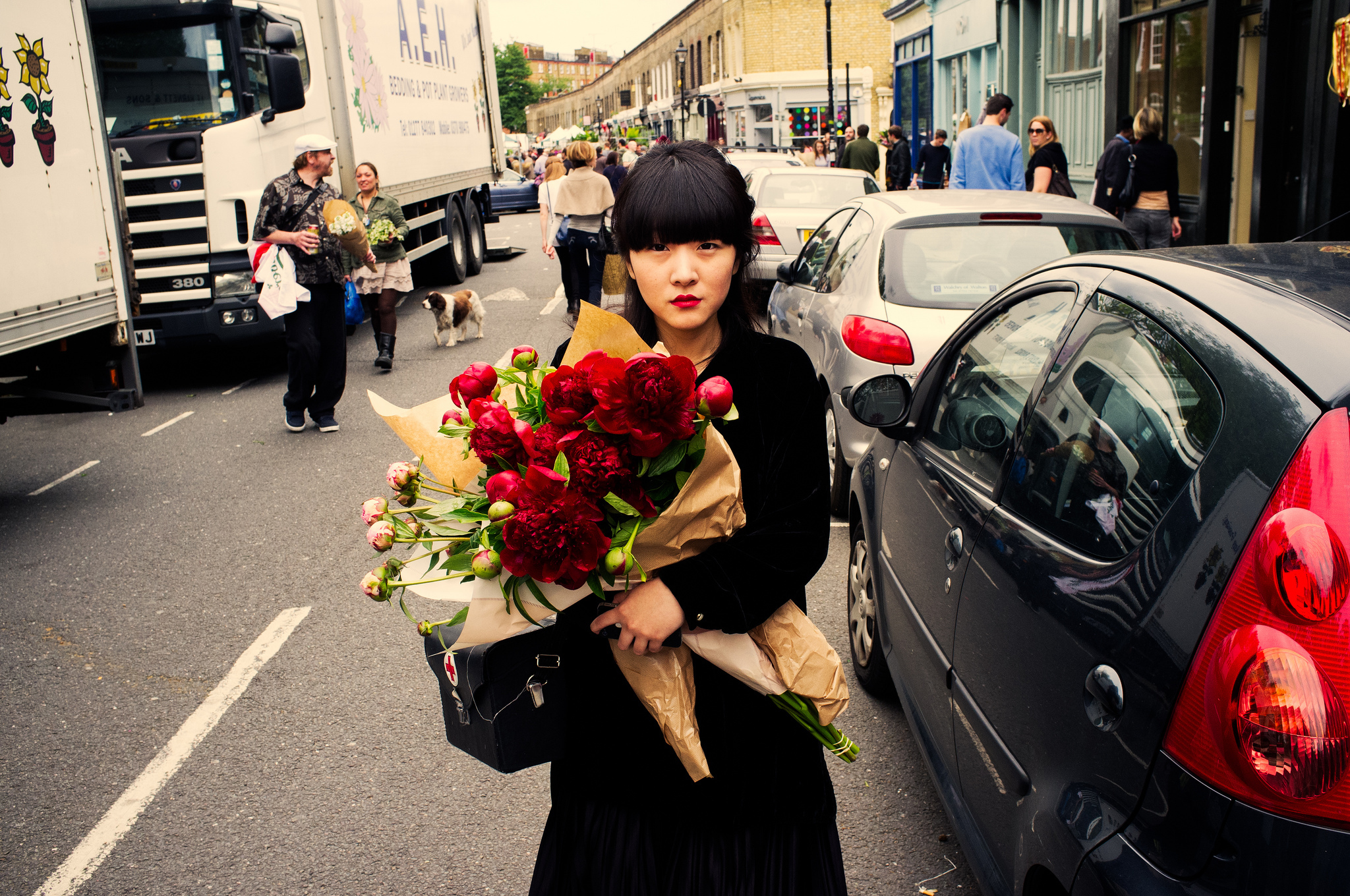 A woman with several bouquets of flowers is captured in this London street portrait.
